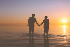 Senior couple walking at sunset Stock Photography