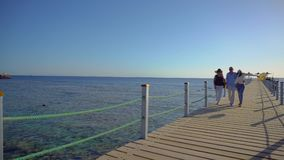 Senior couple walking with their adult daughter on pier by Red sea. Family enjoying vacation. stock footage