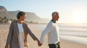 Senior couple walking together on the beach Royalty Free Stock Images