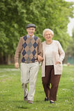 Senior couple walking towards the camera in a park Royalty Free Stock Image