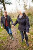 Senior Couple Walking Through Winter Countryside Royalty Free Stock Image