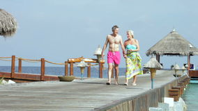 Senior Couple Walking On Wooden Jetty. Senior couple walking along wooden jetty towards camera hand in hand.Shot on Canon 5d Mk2 with a frame rate of 30fps stock footage