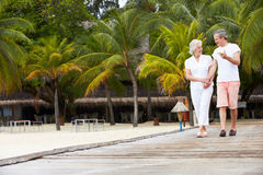 Senior Couple Walking On Wooden Jetty Royalty Free Stock Image