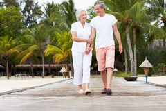 Senior Couple Walking On Wooden Jetty Stock Image