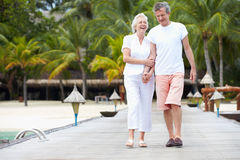 Senior Couple Walking On Wooden Jetty Stock Image