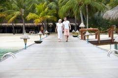 Senior Couple Walking On Wooden Jetty Stock Photography