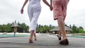 Senior Couple Walking On Wooden Jetty. Senior couple walk past camera position and along wooden jetty into distance.Shot on Canon 5d Mk2 with a frame rate of stock footage