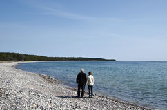 Senior couple walks along coast Royalty Free Stock Photo