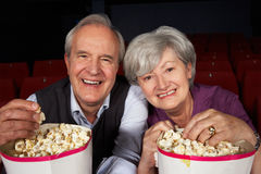Senior Couple Watching Film In Cinema Stock Photo
