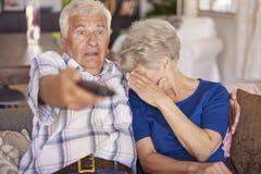 Senior couple watching horror movie Royalty Free Stock Photos
