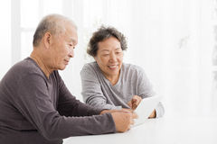 Senior Couple watching the tablet in living room Stock Image