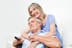 Senior couple watching TV. Together with remote control at home Stock Photos