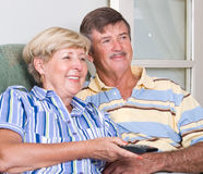 Senior couple watching tv. Happy senior couple watching television together Royalty Free Stock Image