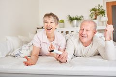 Senior couple watching TV. In bed Stock Photo