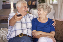 Senior couple watching TV. Every time spent together is very precious Stock Photos