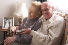 Senior Couple Watching TV At Home. Smiling at tv Royalty Free Stock Photo
