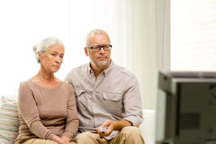Senior couple watching tv at home. Family, technology, age and people concept - senior couple watching tv at home Royalty Free Stock Photo