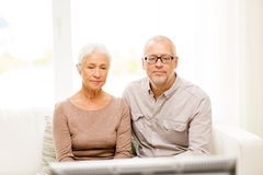 Senior couple watching tv at home. Family, technology, age and people concept - senior couple watching tv at home Royalty Free Stock Photos