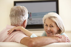 Senior Couple Watching Widescreen TV At Home Royalty Free Stock Photos