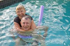 Senior couple water fun. Beautiful relaxed senior couple having fun in a swimming pool Royalty Free Stock Image
