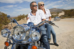 Senior couple wear sunglasses seated on motorcycle on desert road Royalty Free Stock Images