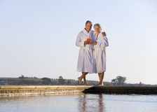 Senior couple wearing white bath robes, embracing outdoors by swimming pool, smiling, portrait Royalty Free Stock Photo