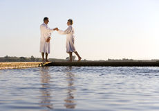 Senior couple wearing white bath robes, standing outdoors by swimming pool, side view Royalty Free Stock Photos
