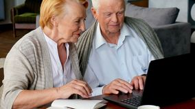 Senior couple websurfing on internet with laptop. Happy elderly man and woman using computer stock footage