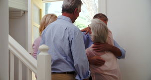 Senior Couple Welcoming Visiting Friends At Front Door stock video footage