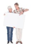 Senior couple with white board. Senior Lovely Couple Holding Together A Blank White Board Over White Background Royalty Free Stock Photo