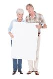 Senior couple with white board. Senior Lovely Couple Holding Together A Blank White Board Over White Background Stock Photo