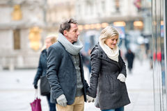 Senior couple window shopping in city centre. Winter Royalty Free Stock Photo