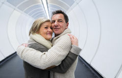 Senior couple in winter clothes in hallway of subway hugging Stock Photography