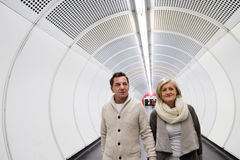 Senior couple in winter clothes walking in hallway of subway Royalty Free Stock Image