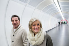 Senior couple in winter clothes walking in hallway of subway Royalty Free Stock Photography