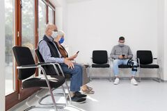 Free Senior Couple With Face Masks Sitting In A Waiting Room Of A Hospital Together With A Young Man Stock Photos - 199015053