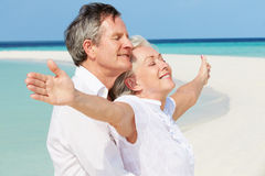 Senior Couple Withs Arms Outstretched On Beautiful Beach Royalty Free Stock Photo