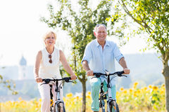 Senior couple, woman and man, riding their bikes Royalty Free Stock Photography