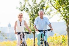 Senior couple, woman and man, riding their bikes Royalty Free Stock Photography