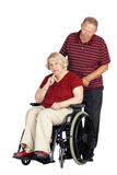 Senior couple with woman in wheelchair. Elderly or senior couple with men caring for his wife in a wheelchair, looking sad or depressed, studio shot isolated Royalty Free Stock Photo
