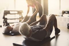 Senior couple workout in rehabilitation center. Personal trainer helps elderly couple to do stretching on the floor Stock Photography