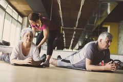 Senior couple workout in rehabilitation center. Personal trainer helps elderly couple to do stretching on the floor Royalty Free Stock Photography
