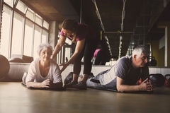Senior couple workout in rehabilitation center. Personal trainer helps elderly couple to do stretching on the floor Stock Photos