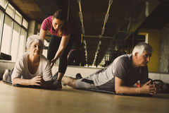 Senior couple workout in rehabilitation center. Personal trainer helps elderly couple to do stretching on the floor Stock Photo