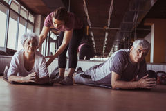 Senior couple workout in rehabilitation center. Personal trainer helps elderly couple to do stretching on the floor Stock Images