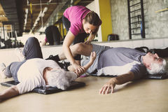 Senior couple workout in rehabilitation center. Personal trainer helps elderly couple to do stretching on the floor Royalty Free Stock Image