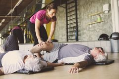 Senior couple workout in rehabilitation center. Personal trainer helps elderly couple to do stretching on the floor Royalty Free Stock Photo