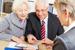 Senior couple writing signature. Under contract after financial consultation Stock Image