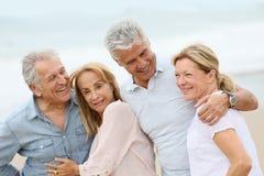 Senior couples enjoying walking on the beach Stock Photos