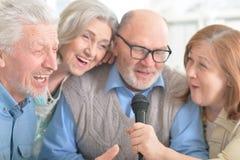 Senior couples reading newspaper. Portrait of two senior couples singing karaoke Stock Photography
